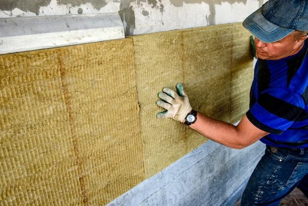 Il lavoratore isola la casa con lastre di lana minerale. isolamento termico interno delle pareti con lana minerale.