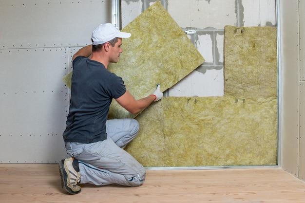 Lavoratore che isola una parete della stanza con isolamento termico in lana di roccia minerale.