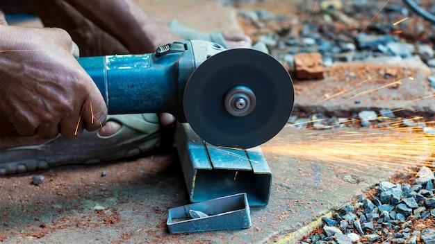 Il lavoratore sta tagliando tubi di acciaio con taglierine in fibra nel lavoro industriale