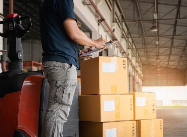Il lavoratore sta facendo la gestione dell'inventario presso il magazzino. le scatole di spedizione controllano le scorte