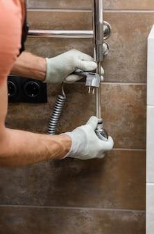 Un operaio sta installando un elemento riscaldante nello scaldasalviette in bagno.