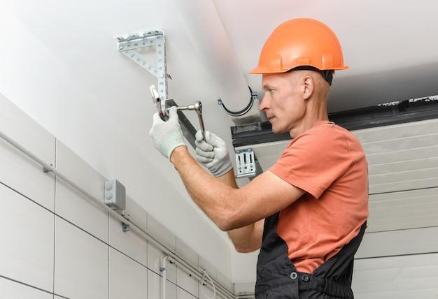 Il lavoratore sta installando i cancelli dell'ascensore nel garage.