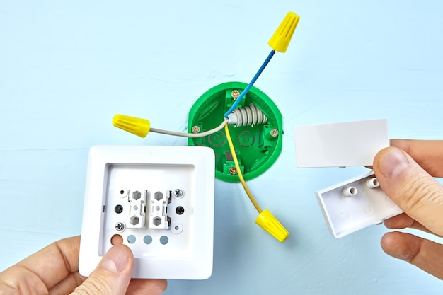 Il lavoratore sta montando un interruttore europeo a due pulsanti, installazione elettrica.