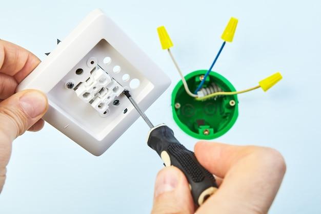 Il lavoratore sta montando un nuovo interruttore a due pulsanti con l'aiuto di uno strumento manuale.