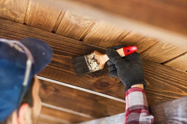 Il lavoratore sta dipingendo la terrazza di legno