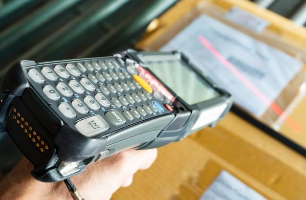 Lavoratore sta scannerizzando scanner di codici a barre con cassette di pacchi.