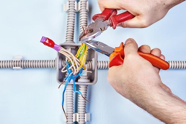 Il lavoratore sta stringendo i fili insieme per un buon contatto con le pinze.