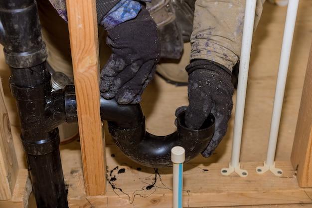 Il lavoratore sta usando la colla con raccordo per l'installazione del tubo di scarico in pvc nell'area di lavoro.
