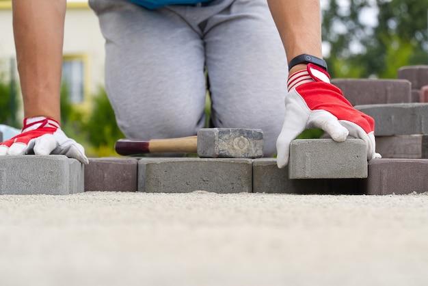 Operaio posa pietre per lastricati. pavimentazione in pietra, operaio edile posa di ciottoli sulla sabbia.