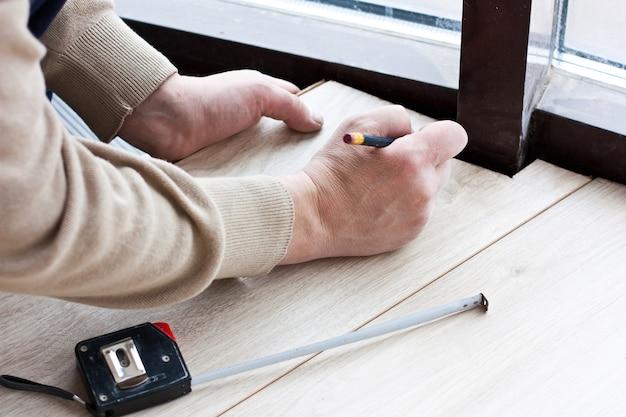 Il lavoratore fa il markup per la posa di pavimenti in laminato