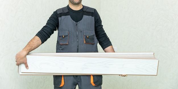 Uomo dell'operaio che tiene laminato di legno bianco