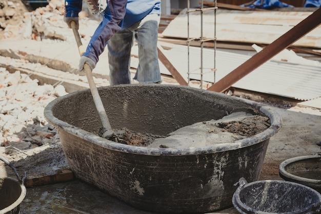 Il muratore della casa dell'uomo del lavoratore mescola il mortaio da un trogolo in secchio