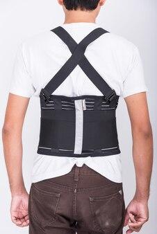 Il corpo dell'uomo dell'operaio indossa la cintura di supporto posteriore per proteggere la postura