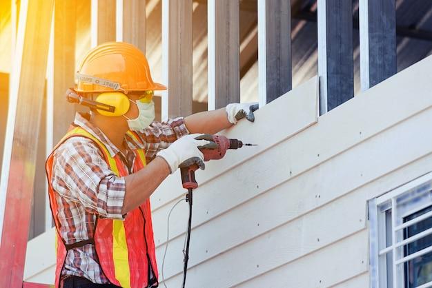 Uomo dell'operaio con casco di sicurezza edilizia edilizia, nuova casa, concetti di servizio interno di costruzione
