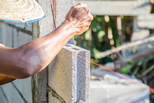La muratura operaia costruisce muri con blocchi di cemento e malta costruendo a strati.