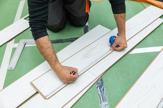 L'operaio misura la lunghezza del laminato di legno bianco