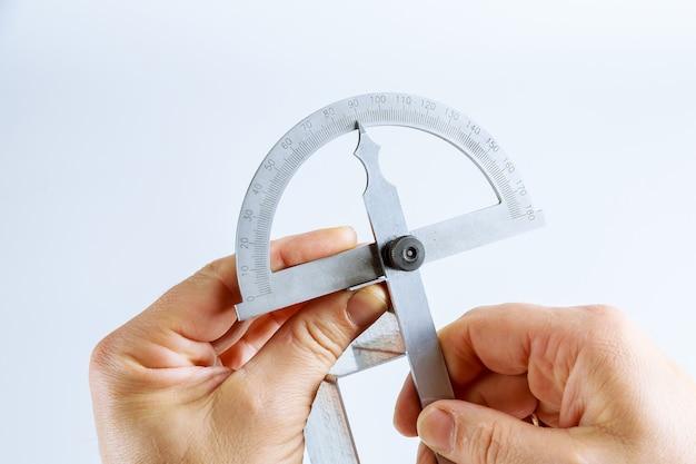 L'operatore misura l'angolo sul prodotto in metallo con un goniometro digitale. strumento e attrezzatura di piegatura della lamiera sottile su una priorità bassa bianca. goniometro digitale.