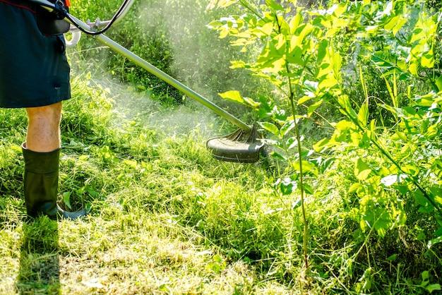 Lavoratore che falcia erba alta con tagliaerba elettrico o a benzina nel parco cittadino o nel cortile strumenti e attrezzature per la cura del giardinaggio processo di taglio del prato con tosaerba manuale