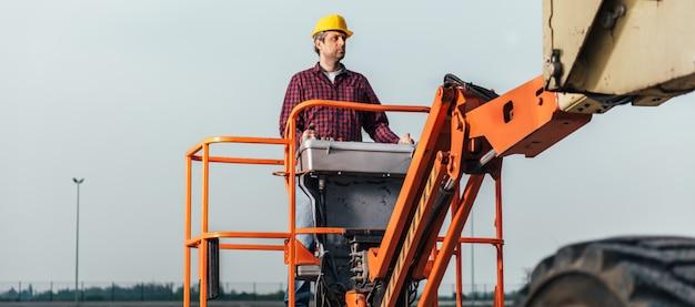 Lavoratore che fa funzionare l'ascensore dell'asta diritto