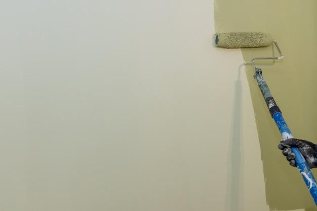 Operaio che dipinge la parete dell'appartamento sulla parete di superficie con la spazzola a rullo