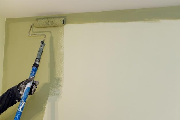 Operaio che dipinge sulla parete superficiale con la pittura a pennello a rullo