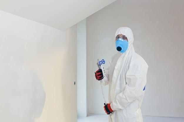 Lavoratore dipinge il muro in una nuova casa con uno spruzzatore
