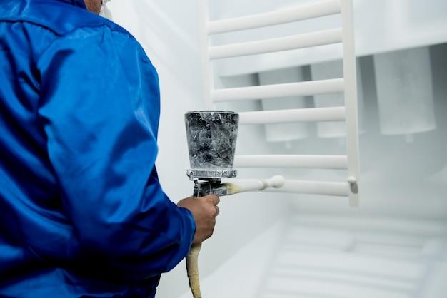 Lavoratore che esegue la verniciatura a polvere di dettagli metallici in fabbrica metallurgica