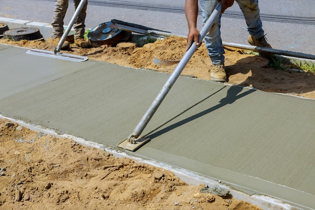 Lavoratore intonacare il cemento cemento durante il marciapiede