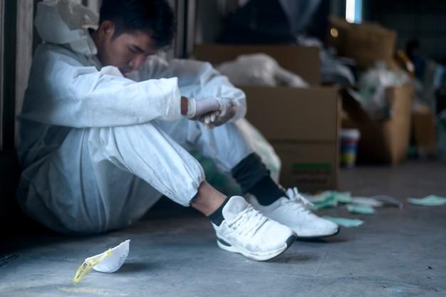 Operaio in dpi esausto e provato negli impianti di riciclaggio dei rifiuti durante il covid-19 e la pandemia.