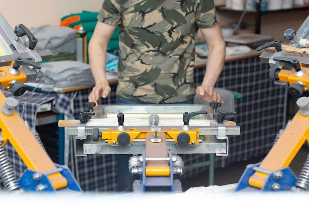 Applicazione dell'immagine di stampa del lavoratore processo di stampa serigrafica serigrafica presso la fabbrica di vestiti. vernici colorate per telaio, tergipavimento e plastisol
