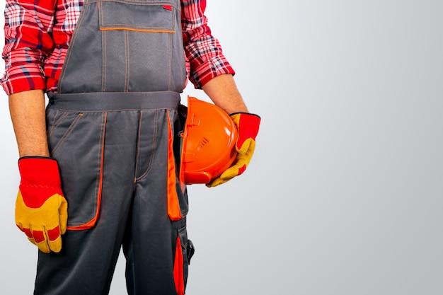 Operaio e costruttore professionale con casco su sfondo grigio con spazio di copia.