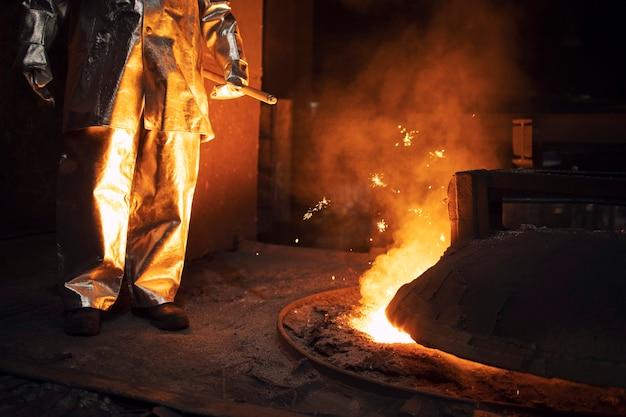 Lavoratore in tuta di protezione che controlla la fusione del ferro nella fornace e applica calore al minerale per estrarre un metallo di base.