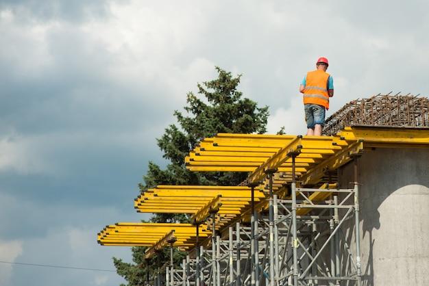 Un lavoratore con un casco protettivo su colonne di cemento installa un telaio rinforzato durante la costruzione di un ponte stradale