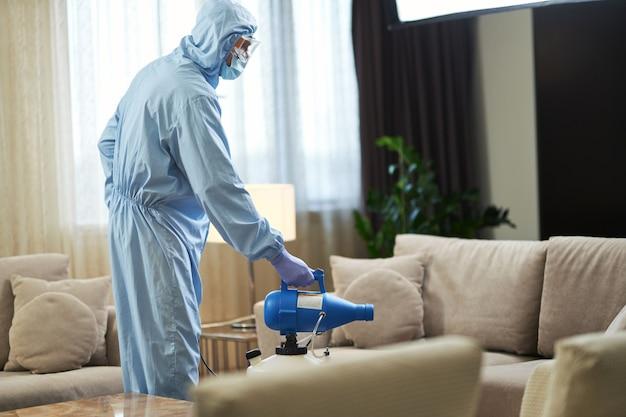 Operaio in tuta protettiva e maschera durante la disinfezione della stanza dai virus. coronavirus e concetto di quarantena