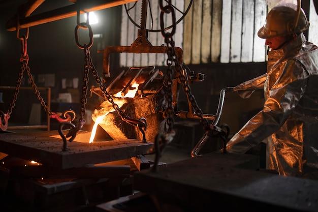 Lavoratore in tuta protettiva che versa acciaio fuso in stampi.