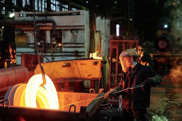 Operaio in abbigliamento protettivo che fonde metallo durante il suo lavoro in fabbrica