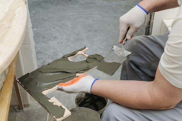 Il lavoratore mette l'adesivo sulla piastrella.