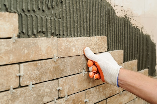 Lavoratore che mette le mattonelle sotto forma di mattone