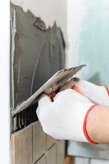 Lavoratore che mette le piastrelle sul muro in cucina.