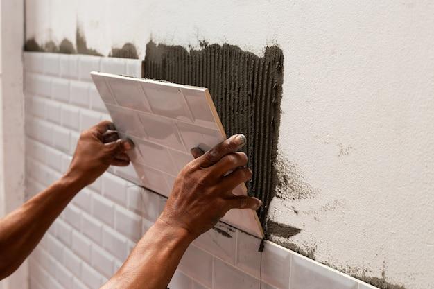 Operaio che mette le piastrelle sul muro.