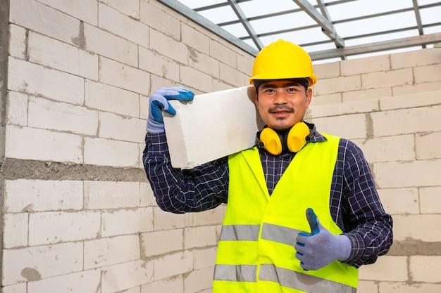 Il lavoratore rassicura detiene mattoni aerati autoclavati in cantiere, concept propone di utilizzare mattoni aerati autoclavati nella costruzione di case.