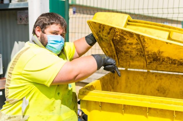 Lavoratore in una fabbrica di riciclaggio o in un punto pulito e immondizia con una maschera facciale e con protezioni di sicurezza. operatore che pulisce e ordina l'installazione