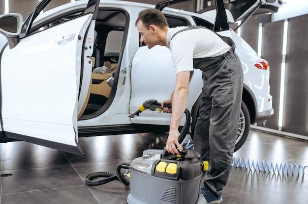 Il lavoratore rimuove lo sporco con l'aspirapolvere, il lavaggio a secco dell'auto e i dettagli.