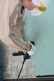 Il lavoratore rimuove la vecchia vernice da un muro di cemento con un martello rotante con uno scalpello, un metodo meccanico per rimuovere la vernice, lavori di riparazione in un appartamento