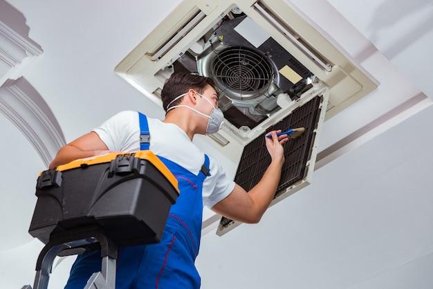 Lavoratore che ripara l'unità di condizionamento d'aria del soffitto
