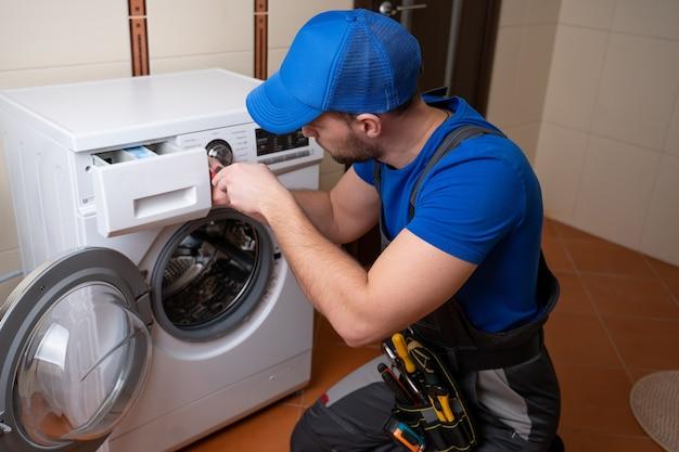 Operaio che ripara lavatrice in lavanderia