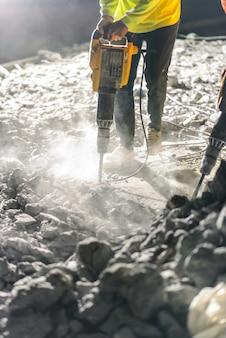 Il lavoratore che ripara lavora con il martello pneumatico alla notte