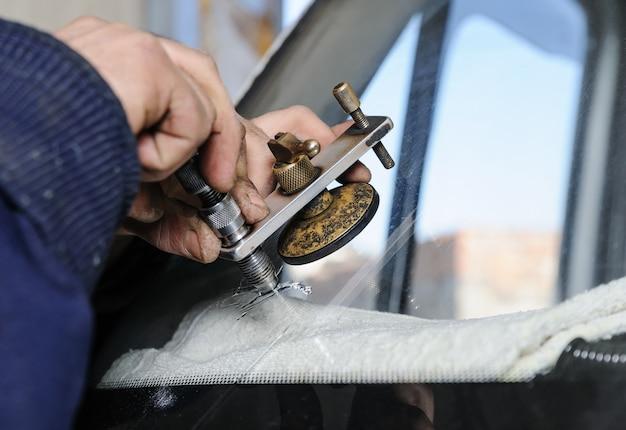 Il lavoratore ripara il parabrezza rotto