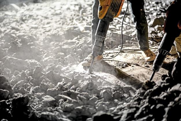 Operaio repaworker che ripara i lavori con il martello pneumatico all'anello notturno funziona con il martello pneumatico