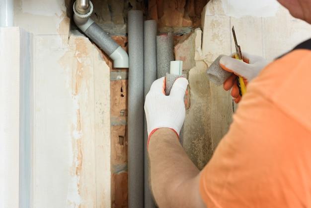 Mano del lavoratore che tiene l'isolamento per i tubi del riscaldamento domestico